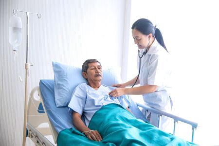 Asian woman professional doctor with notepad smiling, visiting, talking, and diagnosing the old man patient lying in patient's bed at hospital ward Stockfoto
