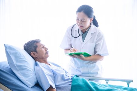 Asian woman professional doctor with notepad smiling, visiting, talking, and diagnosing the old man patient lying in patient's bed at hospital ward Stock fotó