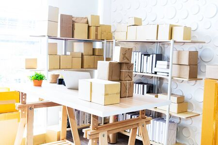 Business start up with Online Business or SME Concept. Working at home,  business start up. Online marketing or Shopping online with box packaging,  parcel box for delivery to customer by logistic service Standard-Bild - 131983696