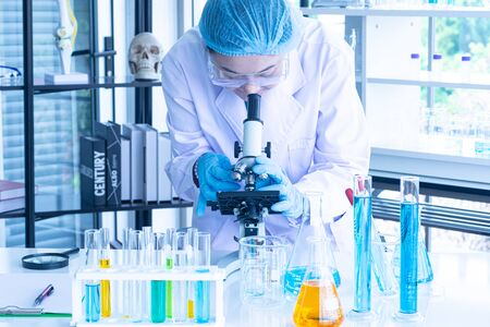 Asian woman scientist, researcher, technician, or student conducted research or experiment by using microscope which is scientific equipment in medical, chemistry or biology laboratory