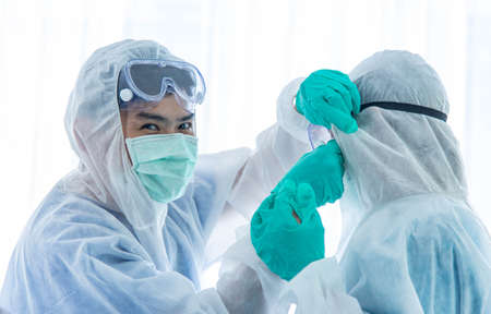 Couple scientists or doctors in protective suit relaxing and taking together in laboratory.