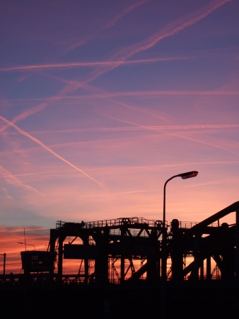 Evening sky with many red contrails over an industrial scene