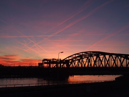 Evening sky with many red contrails over a river and railroad bridge  Stock Photo
