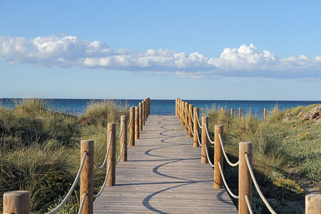 Wooden path towards the sea in Majorcan dune landscape
