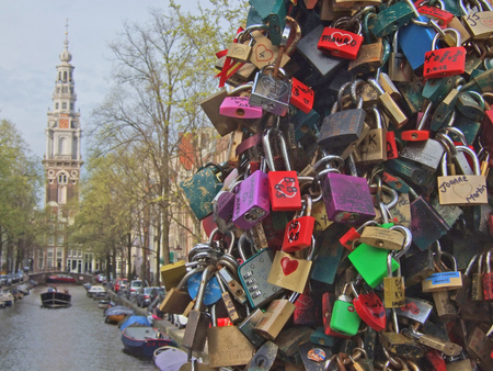 Hundreds of padlocks (called love locks) on a bridge crossing a canal (so called gracht) in Amsterdam, Netherlands. People close these locks on the cables / suspension ropes of the bridge as a sign of eternal love.