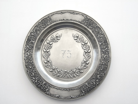Old pewter dish with number 75 and oak and lily ornament