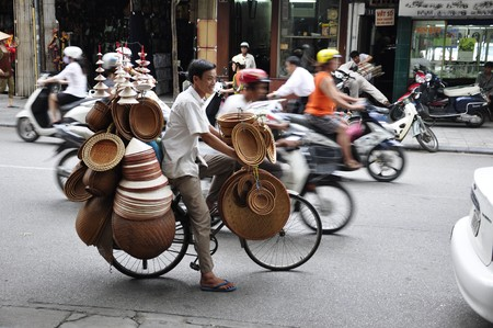 vietnam: Unidentified hat salesman in the busy hanoi traffic on June 29, 2010 in Hanoi, Vietnam