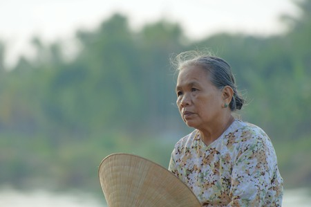 Unidentified woman takes a rest in the early morning sun on July 12, 2010 in Hoi An, Vietnam. Stock Photo