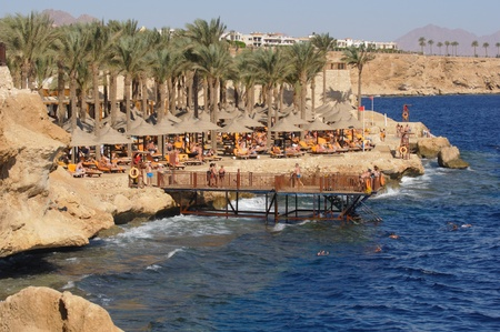 SHARM EL SHEIKH, EGYPT - DECEMBER 01: Unidentified holidaymakers ignores the red flag that tells that bathing is forbidden on December 01, 2010, the day after four Russian holidaymakers were badly injured at the coastline in Sharm El Sheikh, Egypt. They a