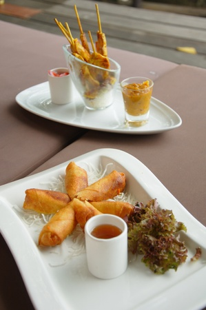 samui: Spring rolls on a plate with a chicken satay plate in the background on a resort at Lamay, Koh Samui in Thailand
