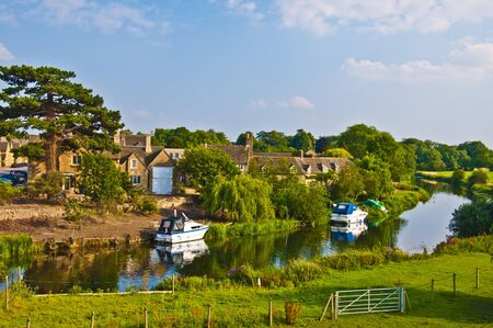 Old English village next to river on a summers evening photo