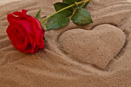 genegenheid: Rode roos op het strand met een hart in het zand Stockfoto