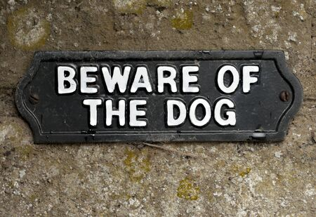 Beware of the dog sign screwed onto stone photo