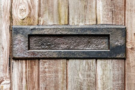 panelled: Old letter box in a wooden panelled door