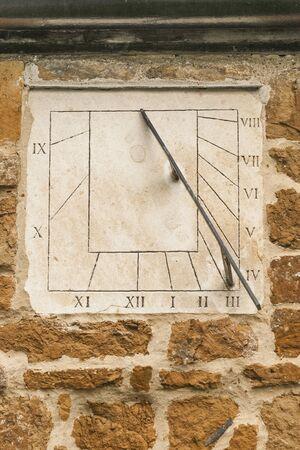 sun dial: Modern stone sun dial set in a stone wallwith Roman numerals