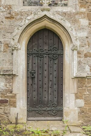 Old dark Church door with a pointed stone archway set in stone photo
