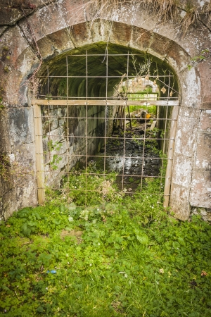 culvert: Old arched culvert in an old stone wall