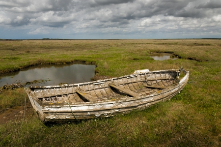 rotting: Old rotting wooden rowing boat at Brancaster Norfolk England