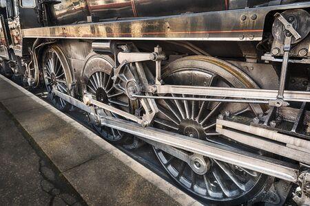 beneath: Old steam engine wheels beneath a steam train Stock Photo