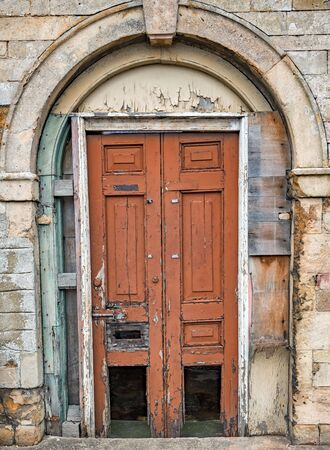 decaying: Old decaying wooden double doors in a stone archway