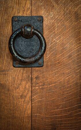 doorknocker: Old black metal circular knocker on oak door Stock Photo
