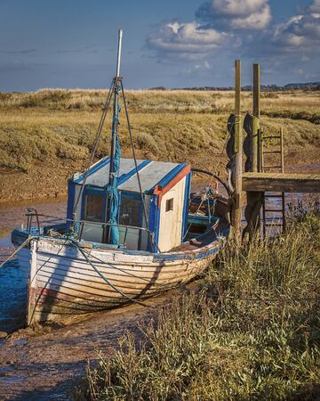 moored: Old decaying wooden fishing boat moored up