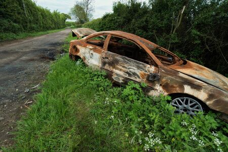 grass verge: Burnt out rusty old car pushed off the road into the grass verge Stock Photo