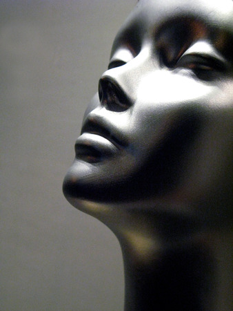 dramatically: close-up of silver mannequin in studio with face looking up dramatically