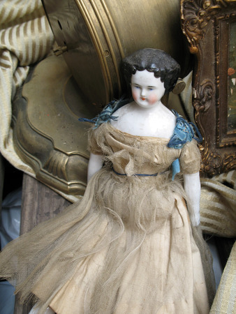 18th Century Victorian doll with orginal dress next to antique bronze clock and old picture frame shot in natural daylight