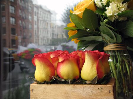 arrangment: Wooden box of three symetric red and yellow roses next to silver metal background reflecting city buildings from outside and another vase of yellow and white flowers. Stock Photo