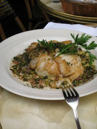 Gourmet plate of Monkfish with capers and onions on white plate with a silver fork