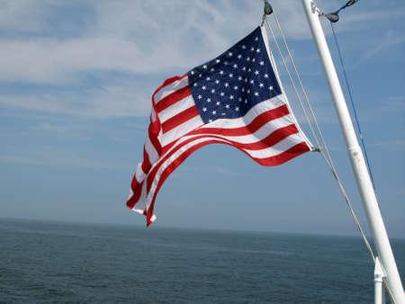 American flag blowing agaisnt blue sky above ocean water Banco de Imagens