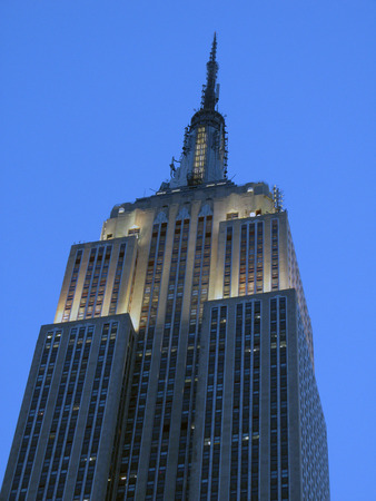 Close-up of the top of the Empire State Building at night with white lights