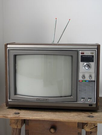 Old antique box television with antenna on wood table