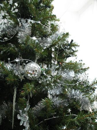 Silver ornaments and garland on a Christmas tree