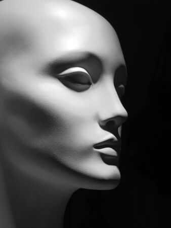 Black and white image of a white mannequin head on a black background