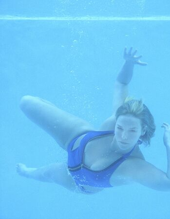 Plus size blonde girl in blue swimsuit underwater in pool