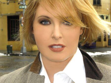 베이지 색 재킷 밖에 금발 소녀의 근접 아름다움