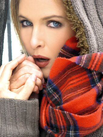 checked: Blonde Girl blowing her hands to keep warm in green hooded sweater and red checked scarf