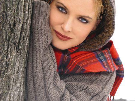 올리브 스웨터와 체크 무늬 스카프에 나무의 기울고 여자의 아름다움 이미지