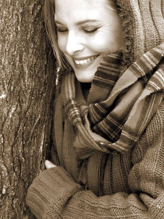 Blonde girl looking down in fashion sweater smiling in black and white sepia toned Stok Fotoğraf
