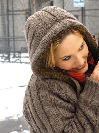 웃 고 겨울 복장, 두건을 된 스웨터와 빨간색 스카프에 웃 고 금발 소녀