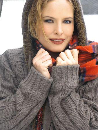 겨울에 체크 스카프와 어두운 녹색 두건을 된 스웨터에 빛 메이크업과 금발 소녀의 아름다움
