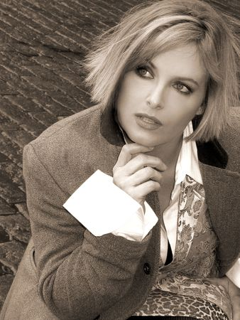 Sepia Tone image of Blonde girl in fashion outfit tailored coat and vest with wide white cuffs Stok Fotoğraf