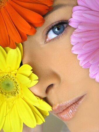 cuffs: Close-up of girls face with smirk showing multi-colored flowers and one blue eye Stock Photo
