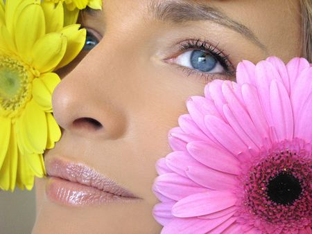 blonde blue eyes: Close-up beauty of blue eye woman natural make-up and large flowers inside with daylight Stock Photo