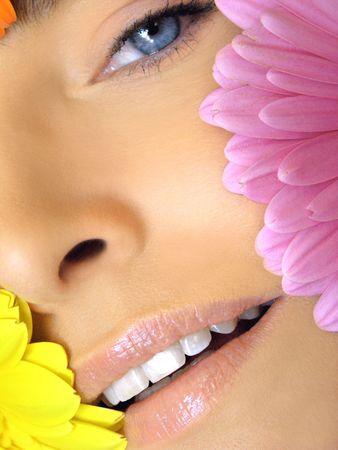 Extreme close-up of woman with pedal edges of yellow and pink flowers with natural make-up smiling