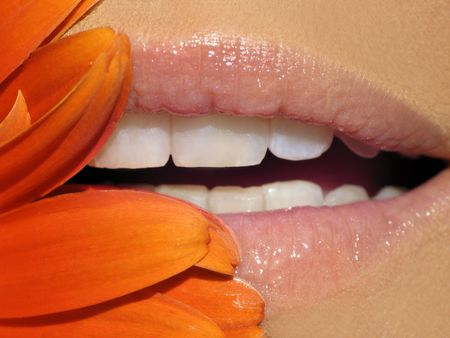 Close-up of sparkling lipgloss in bright sunlight with orange flower pedals