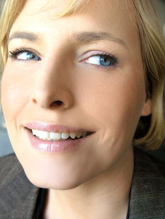 perfect face: Close-up image of blonde blue-eyed woman in business jacket smiling looking over her shoulder Stock Photo