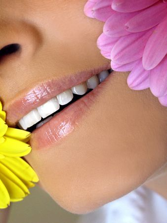 blonde blue eyes: Extreme close-up of smiling mouth with perfect teeth and flower pedals Stock Photo